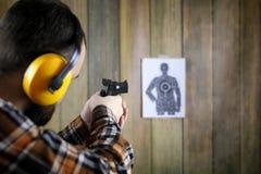 Человек с положенными дальше защитными изумлёнными взглядами и тренировка уха в пистолете sh Стоковое Изображение