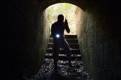 Человек с радиоприемником и электрофонарем входит в тоннель Стоковое Фото
