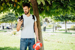 Человек с рюкзаком и подарком рядом с деревом стоковое фото