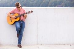 Человек с склонностью гитары на стене Стоковые Фото