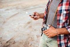 Человек с старой винтажной камерой фото используя сотовый телефон Стоковое Фото