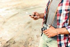 Человек с старой винтажной камерой фото используя сотовый телефон Стоковое фото RF