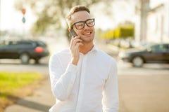 Человек с стеклами говорит на мобильном телефоне в руках Стоковые Фото