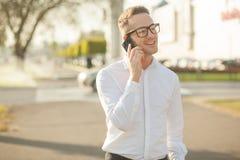 Человек с стеклами говорит на мобильном телефоне в руках Стоковое Изображение