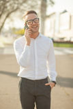Человек с стеклами говорит на мобильном телефоне в руках Стоковое фото RF