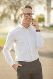 Человек с стеклами говорит на мобильном телефоне в руках Стоковая Фотография