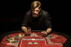 Человек с стеклом питья спирта и обломока покера в руках сидя на таблице покера Стоковые Изображения