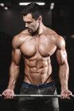 Человек с тренировкой веса в спортивном клубе оборудования спортзала Стоковые Изображения RF
