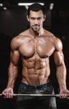 Человек с тренировкой веса в спортивном клубе оборудования спортзала Стоковые Изображения