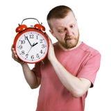 Человек слушая к тикать будильника стоковые фотографии rf