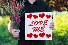 Человек с цветками и доска любят меня Стоковые Фото