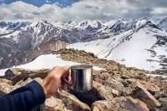 Человек с чашкой в горах стоковые фотографии rf