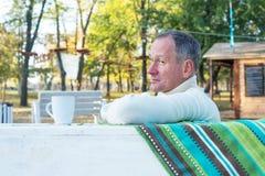 Человек с чашкой кофе в парке осени Стоковые Изображения