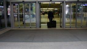 Человек с 2 чемоданами входит в станцию сток-видео