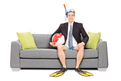 Человек с шноркелем и деловой костюм усаженный на софу Стоковая Фотография