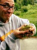 Человек с grinning выражение держа большой лягушка-бык Стоковое Изображение RF