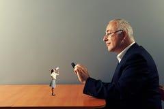 Человек с loupe и малой женщиной Стоковые Фотографии RF