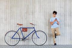 Человек с smartphone и фиксированная шестерня велосипед на улице Стоковая Фотография