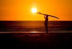 Человек с surfboard в заходе солнца на пляже Стоковое Изображение RF