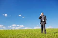Человек телефонируя в солнечном зеленом поле стоковое фото