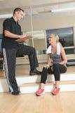 Человек тренера женщины спортзала личный с весом Стоковое фото RF