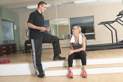 Человек тренера женщины спортзала личный с весом Стоковая Фотография