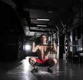 Человек тренировки сидения на корточках фронта штанги атлетический во время интенсивной разминки Стоковое Фото