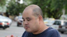 Человек тучной азиатской лысой головы тайский сдерживающ и ел drumstick жареной курицы жадно с голодом с потом воды на его сторон сток-видео