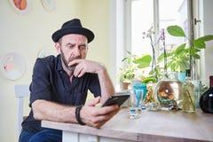 Человек думая и холя над smartphone Стоковые Фото