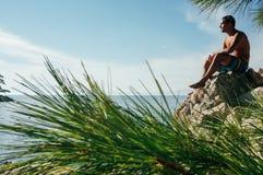Человек думая на скале Стоковое Изображение RF
