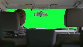 Человек управляет автомобилем против зеленой предпосылки акции видеоматериалы