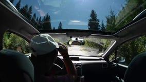 Человек управляя автомобилем на проселочной дороге