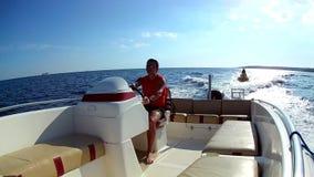 Человек управляя моторной лодкой видеоматериал