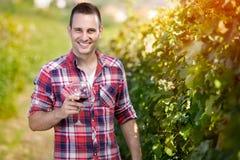 Человек усмехаясь и держа бокал вина Стоковая Фотография