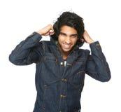 Человек усмехаясь и держа воротник куртки джинсовой ткани стоковые изображения