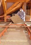 Человек устанавливает термоизоляцию rockwool между деревянным scaffoldin Стоковые Изображения RF