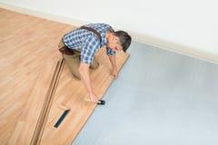 Человек устанавливая новый прокатанный деревянный пол стоковые изображения