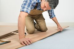 Человек устанавливая новый прокатанный деревянный пол стоковая фотография rf