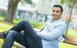 Человек улыбки детенышей счастливый сидя на стенде Стоковое Изображение RF