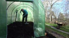 Человек фермера выравнивая почву с инструментом грабл в парнике 4K видеоматериал