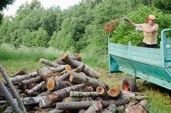 Человек фермера разгржает швырок журналов дерева от трейлера Стоковые Фотографии RF