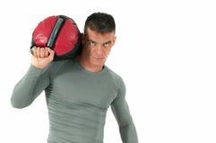 Человек фитнеса в плотной рубашке представляя с мешком песка на его плече Стоковое Фото