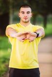 Человек фитнеса протягивая плечо руки перед внешней разминкой Sporty мужской спортсмен в городском парке нагревая стоковые изображения