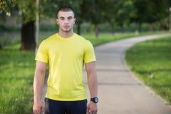 Человек фитнеса протягивая плечо руки перед внешней разминкой Sporty мужской спортсмен в городском парке нагревая стоковые изображения rf