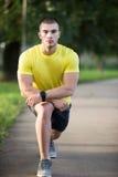 Человек фитнеса протягивая плечо руки перед внешней разминкой Sporty мужской спортсмен в городском парке нагревая стоковые фотографии rf