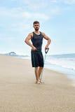 Человек фитнеса работая на пляже, делая тренировку детандера внешнюю Стоковое фото RF