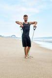 Человек фитнеса работая на пляже, делая тренировку детандера внешнюю Стоковые Изображения