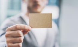 Человек фото крупного плана нося вскользь рубашку и показывая пустую визитную карточку ремесла запачканная предпосылка Подготавли Стоковая Фотография RF