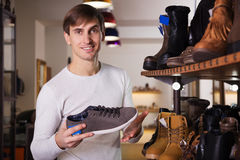 Человек хочет купить ботинки Стоковые Изображения