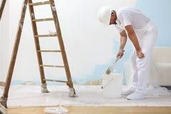 Человек художника на работе принимает цвет с кистью от бушеля Стоковое фото RF